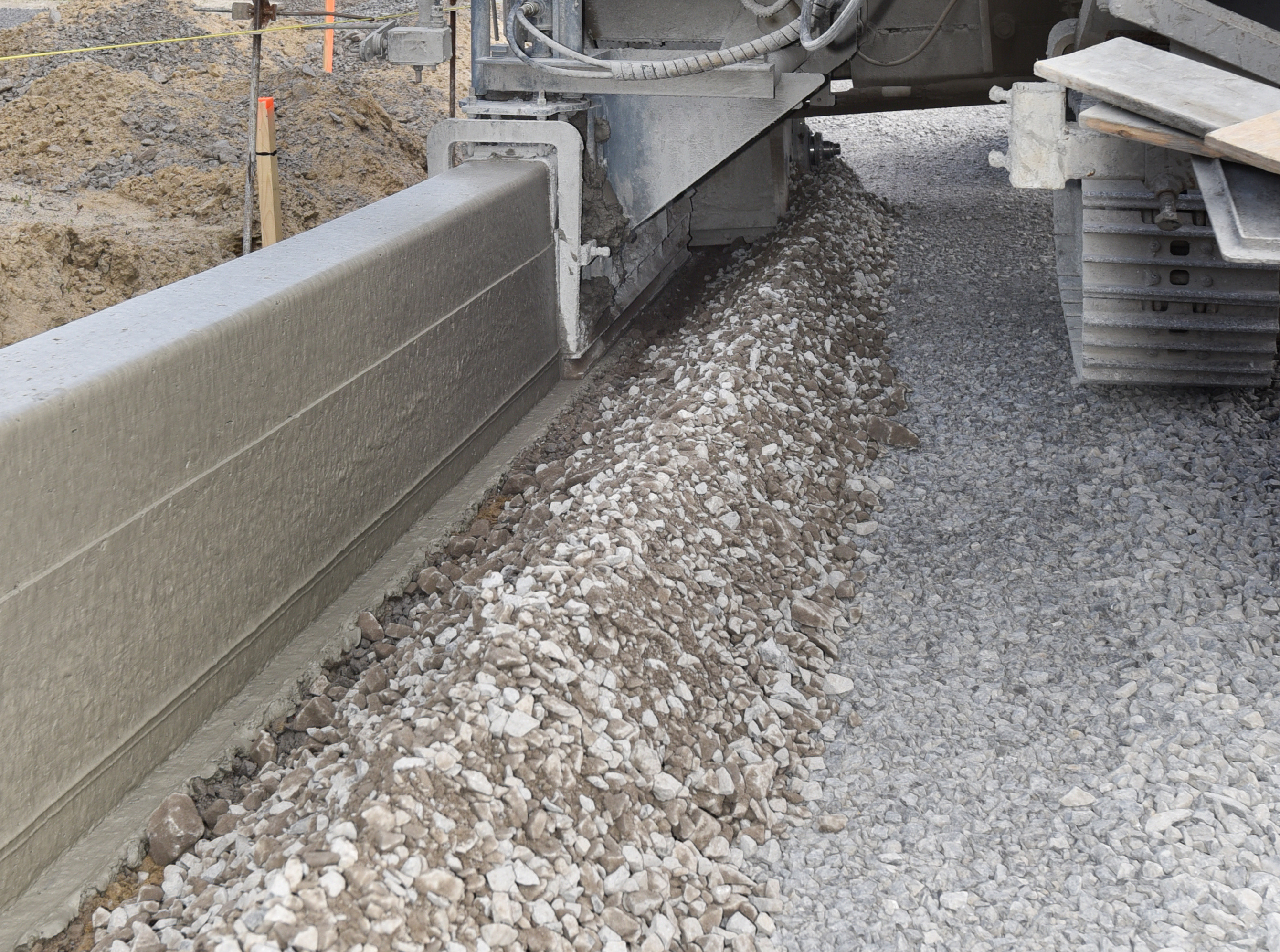 Machine extruding concrete on construction site with concrete fibers
